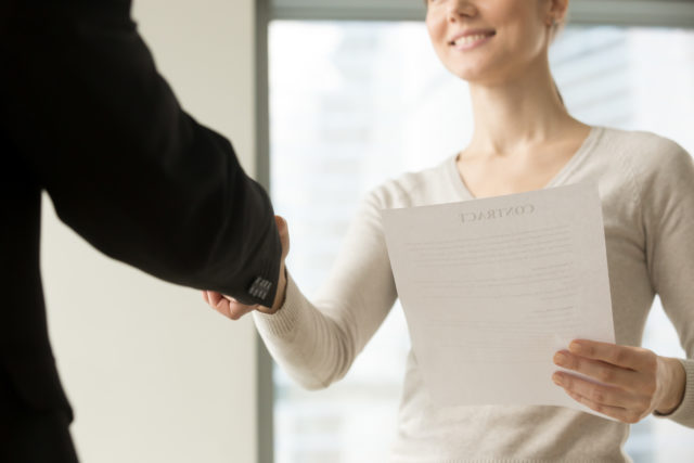 Female business leader holding contract document and shaking hand with colleague before or after negotiation. Businesswoman concluding agreement, starting partnership, accepting offer. Close up view